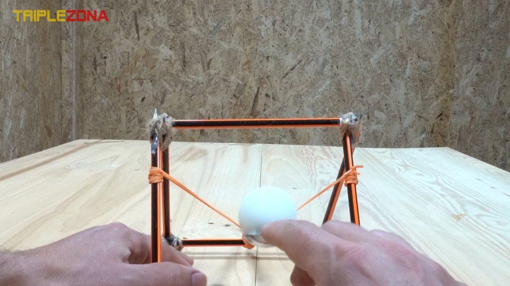 Pelota de ping pong lanzada por catapulta de lápices